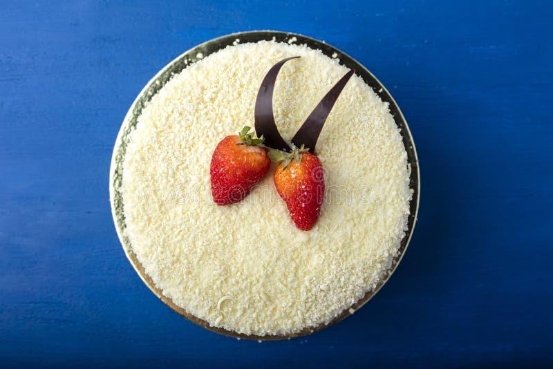 Torta con el chocolate blanco y las fresas frescas Postre delicioso en un fondo azul imagen de archivo libre de regalías