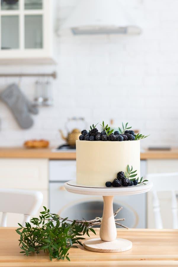 Torta con el queso cremoso, los arándanos frescos y las zarzamoras en la tabla de madera en la cocina Pastel de bodas, torta de c fotografía de archivo