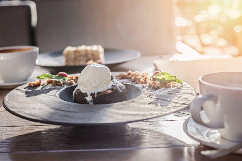 Torta con gelato in piastra nera e tazza bianca di caffè delizioso sul tavolo di legno alla luce del tramonto fotografia stock libera da diritti
