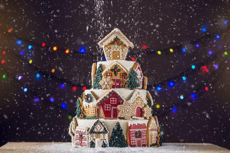 Torta con gradas grande de la Navidad adornada con las galletas del pan de jengibre y una casa en el top Árbol y guirnaldas en el foto de archivo