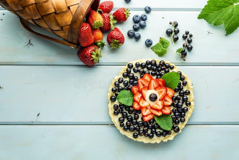 Torta con la empanada de las bayas con las fresas y las grosellas negras en la tabla rústica azul foto de archivo libre de regalías
