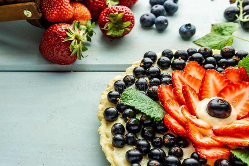 Torta con la empanada de las bayas con las fresas y las grosellas negras en la tabla rústica azul fotos de archivo