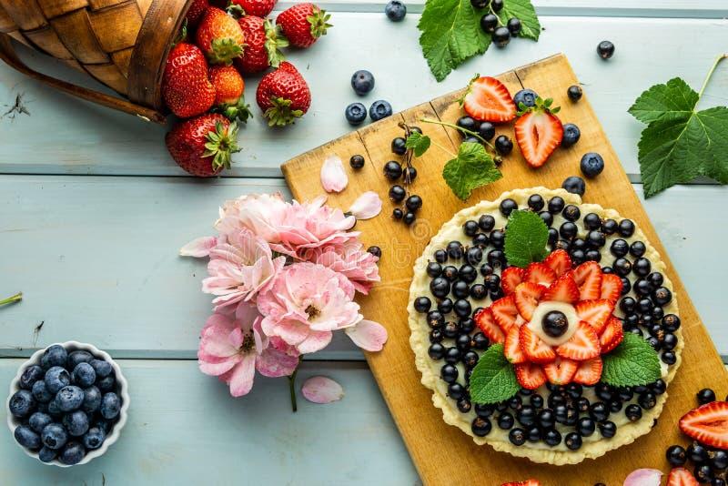 Torta con la empanada de las bayas con las fresas y las grosellas negras en la tabla rústica azul imagen de archivo