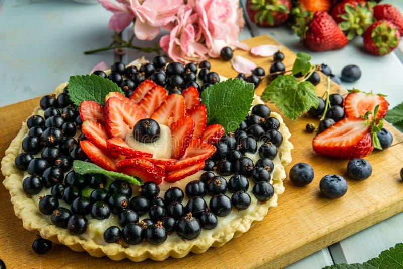 Torta con la empanada de las bayas con las fresas y las grosellas negras en la tabla rústica azul fotografía de archivo libre de regalías
