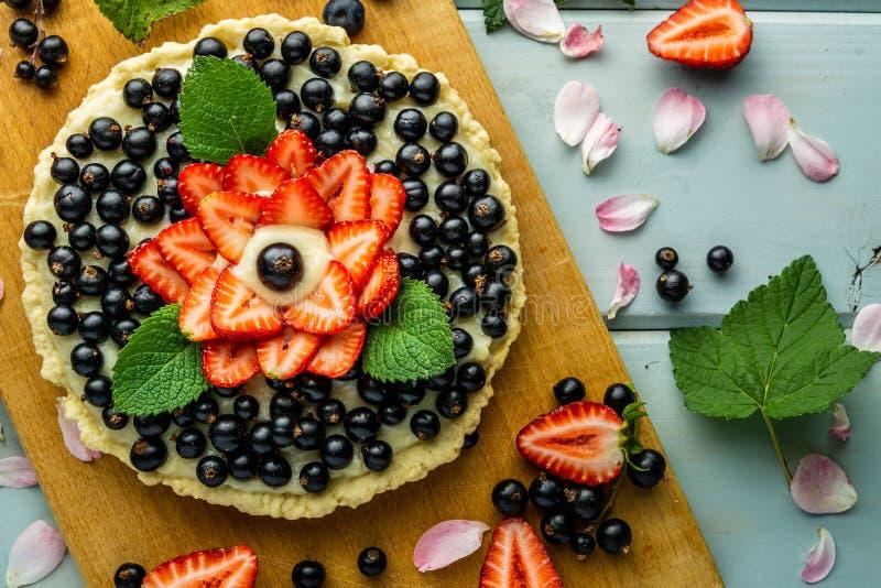 Torta con la empanada de las bayas con las fresas y las grosellas negras en la tabla rústica azul fotografía de archivo