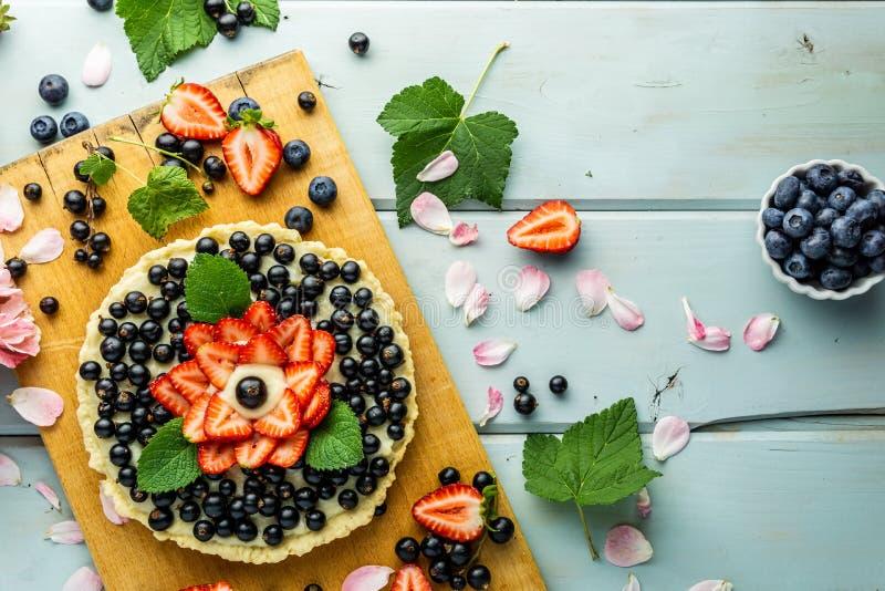 Torta con la empanada de las bayas con las fresas y las grosellas negras en la tabla rústica azul imágenes de archivo libres de regalías