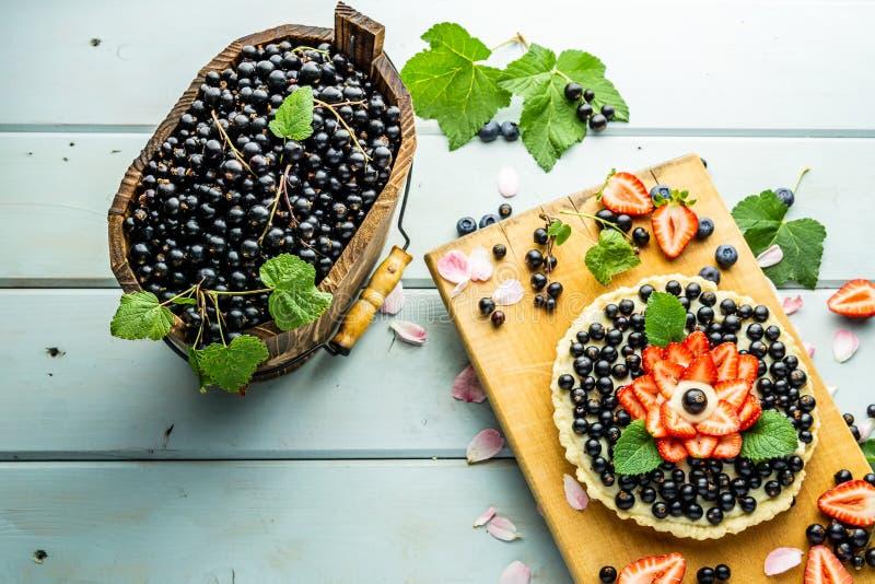 Torta con la empanada de las bayas con las fresas y las grosellas negras en la tabla rústica azul fotos de archivo libres de regalías