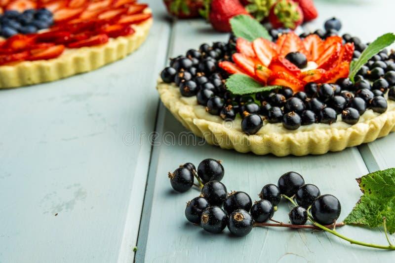 Torta con la empanada de las bayas con las fresas y las grosellas negras en la tabla rústica azul imagenes de archivo