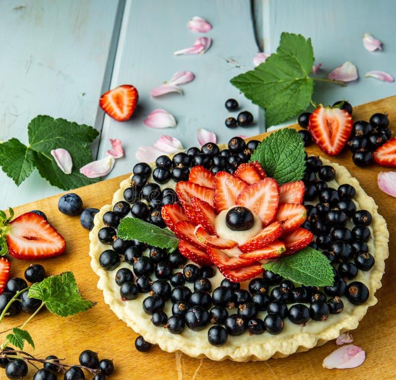 Torta con la empanada de las bayas con las fresas y las grosellas negras en la tabla rústica azul foto de archivo