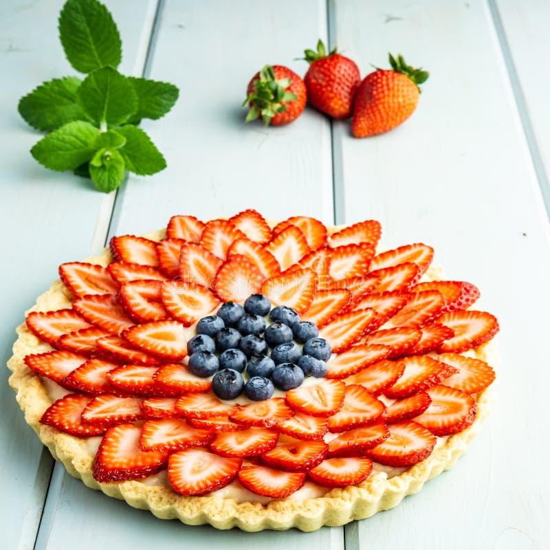 Torta con la empanada de las bayas con las fresas y los arándanos en la tabla rústica azul fotos de archivo libres de regalías