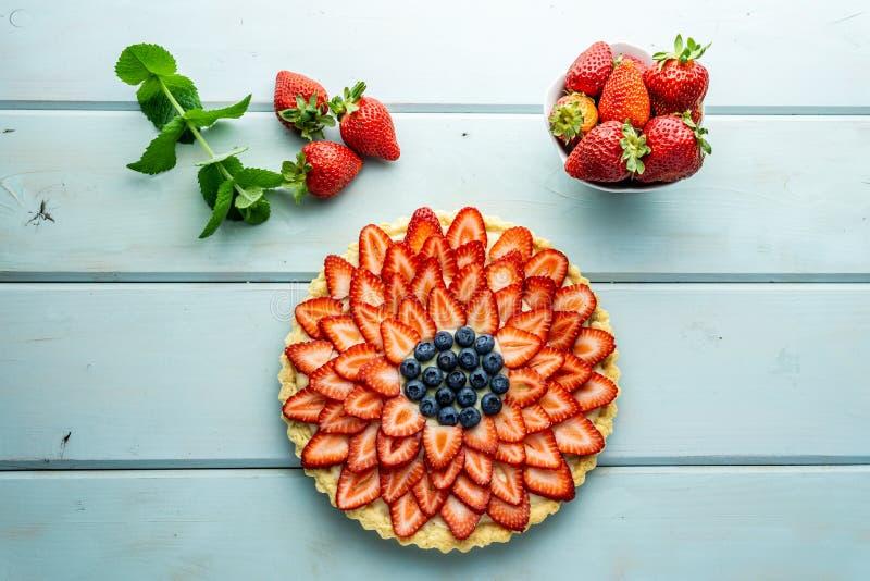 Torta con la empanada de las bayas con las fresas y los arándanos en la tabla rústica azul fotografía de archivo