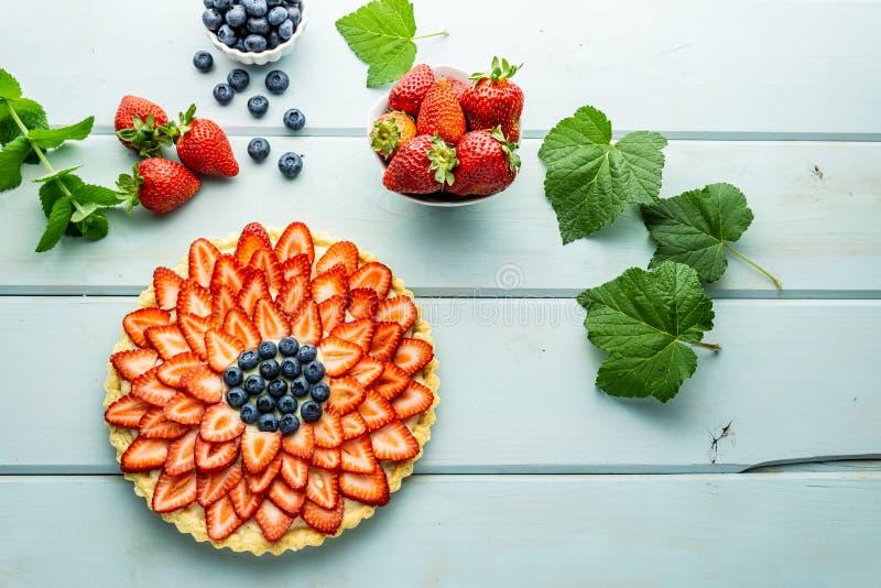Torta con la empanada de las bayas con las fresas y los arándanos en la tabla rústica azul imagenes de archivo