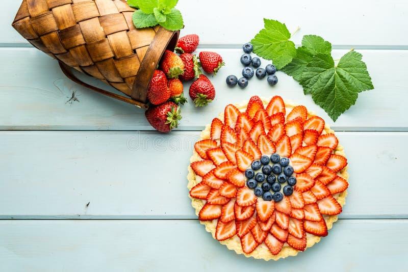 Torta con la empanada de las bayas con las fresas y los arándanos en la tabla rústica azul imágenes de archivo libres de regalías
