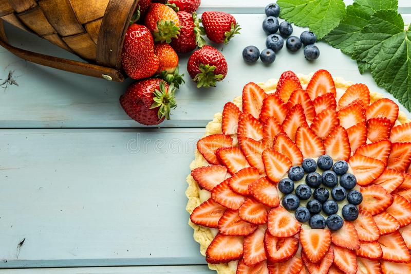 Torta con la empanada de las bayas con las fresas y los arándanos en la tabla rústica azul fotografía de archivo libre de regalías