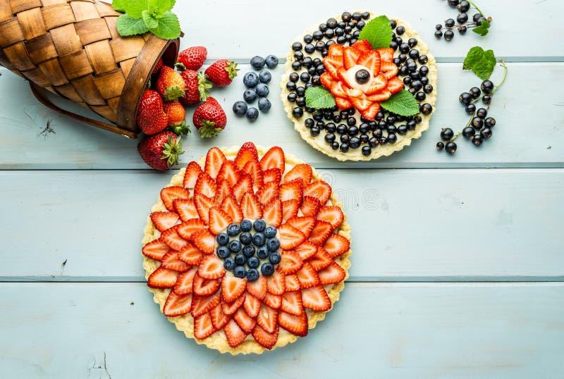 Torta con la empanada de las bayas con las fresas y los arándanos en la tabla rústica azul fotos de archivo