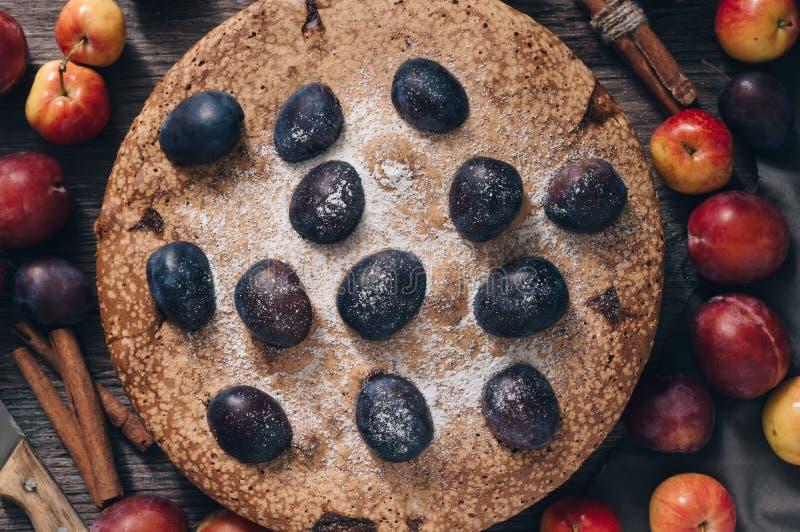 Torta con la fruta, visión superior Empanada con los ciruelos y las manzanas en una tabla de madera fotografía de archivo