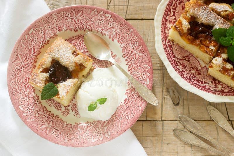 Torta con le prugne e le pesche, servite con una palla del gelato alla vaniglia e le foglie della melissa immagini stock libere da diritti