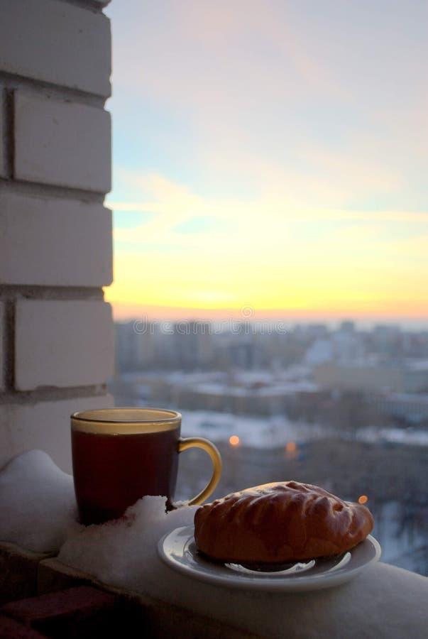 Torta corado e uma caneca de chá quente em um fundo borrado do por do sol fotografia de stock royalty free