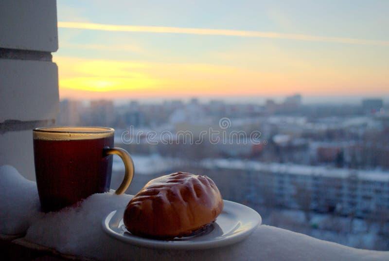 Torta corado e uma caneca de chá quente em um fundo borrado do por do sol foto de stock royalty free