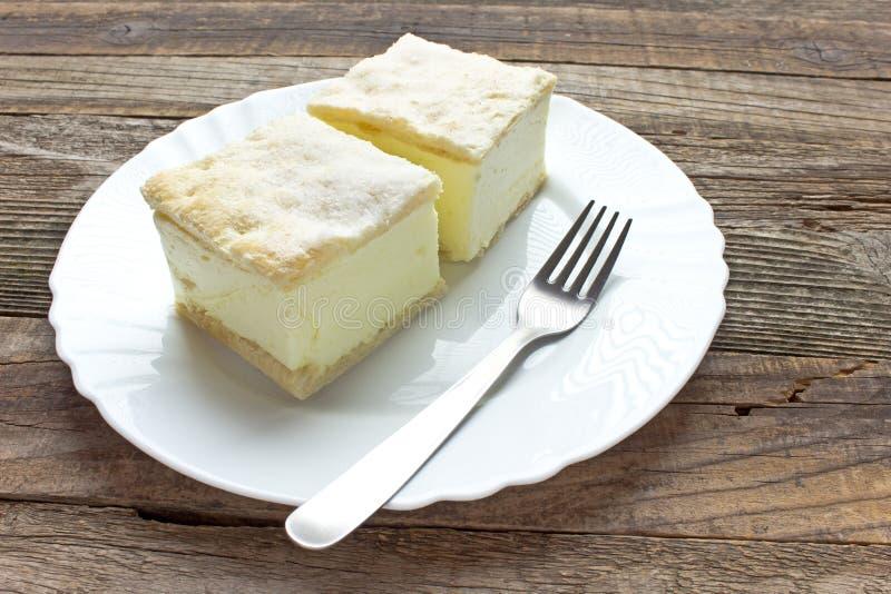 Torta crema con gli strati della pasta sfoglia in piatto immagini stock