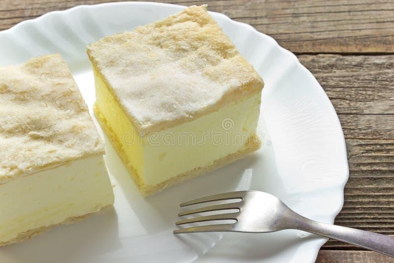 Torta crema con gli strati della pasta sfoglia in piatto fotografia stock