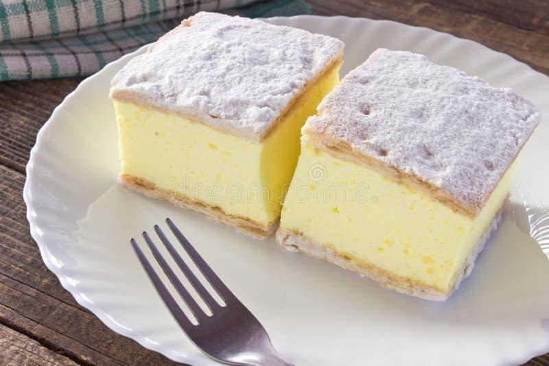 Torta crema con gli strati della pasta sfoglia in piatto sulla tavola di legno immagine stock libera da diritti