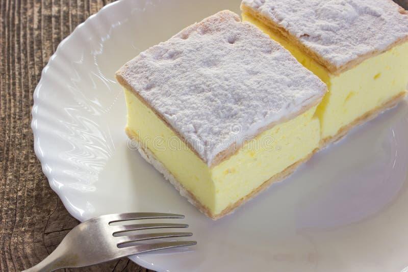 Torta crema con gli strati della pasta sfoglia in piatto sulla tavola di legno immagine stock