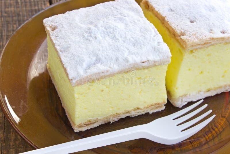 Torta crema con gli strati della pasta sfoglia in piatto sulla tavola di legno immagini stock libere da diritti