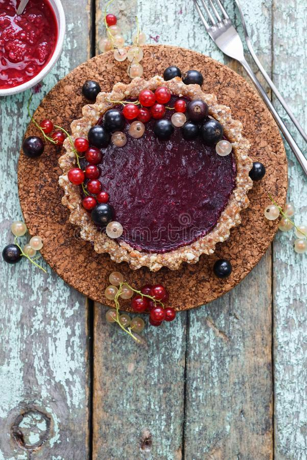 Torta cruda del vegano con l'inceppamento della bacca e l'uva passa organica su backgr blu fotografie stock libere da diritti