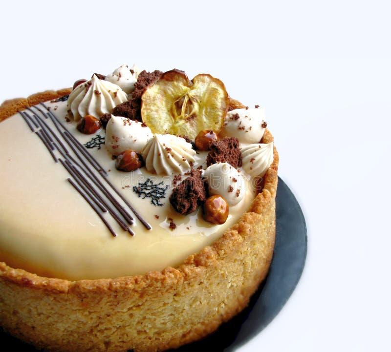 Torta de Apple y del caramelo con las avellanas y la frontera de la galleta en el práctico de costa negro imágenes de archivo libres de regalías