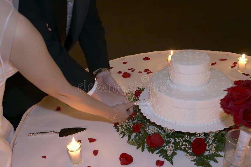 Torta de boda del corte de novia y del novio de Candlelight fotos de archivo libres de regalías