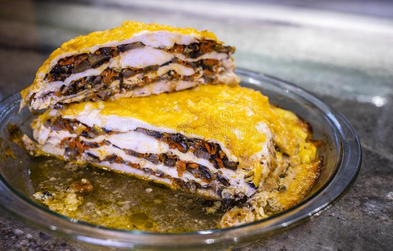 A torta de carne cozida apetitosa com os cogumelos e os vegetais cobertos com queijo derretido está na tabela na bandeja de vidro imagens de stock royalty free