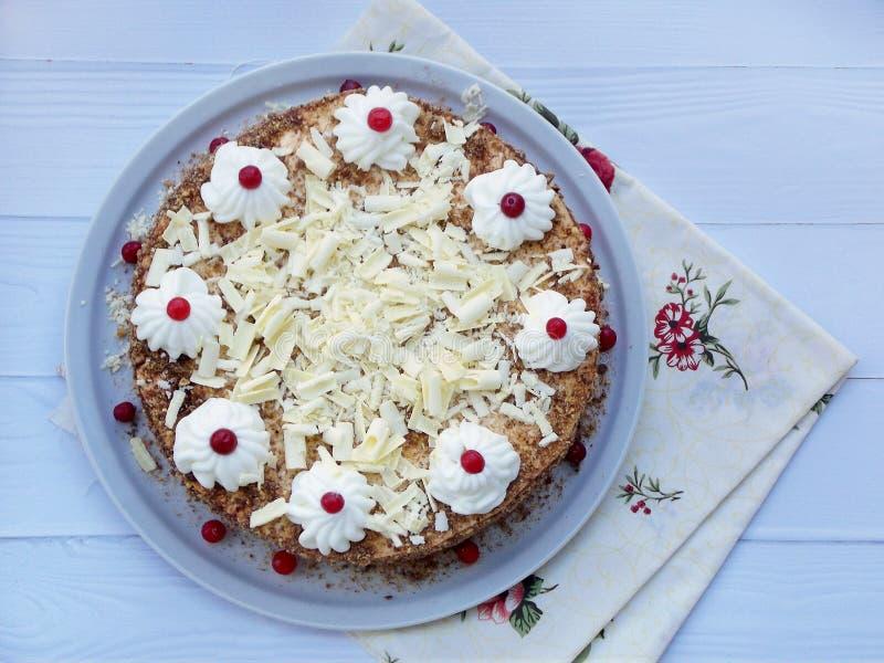 Torta de chocolate adornada con los rosetones de la crema y de las bayas en un fondo de madera fotos de archivo