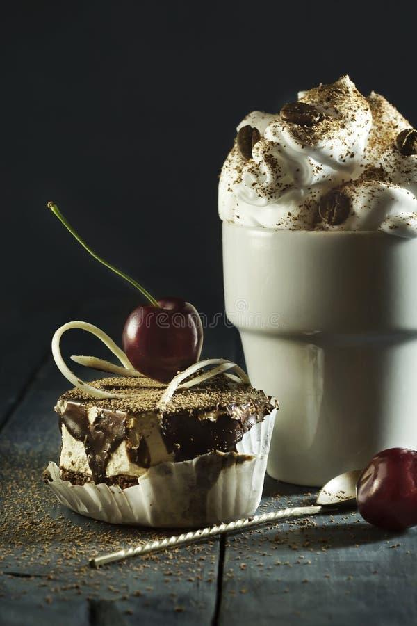 Torta de chocolate con cerezas y una taza de café con crema azotada foto de archivo libre de regalías
