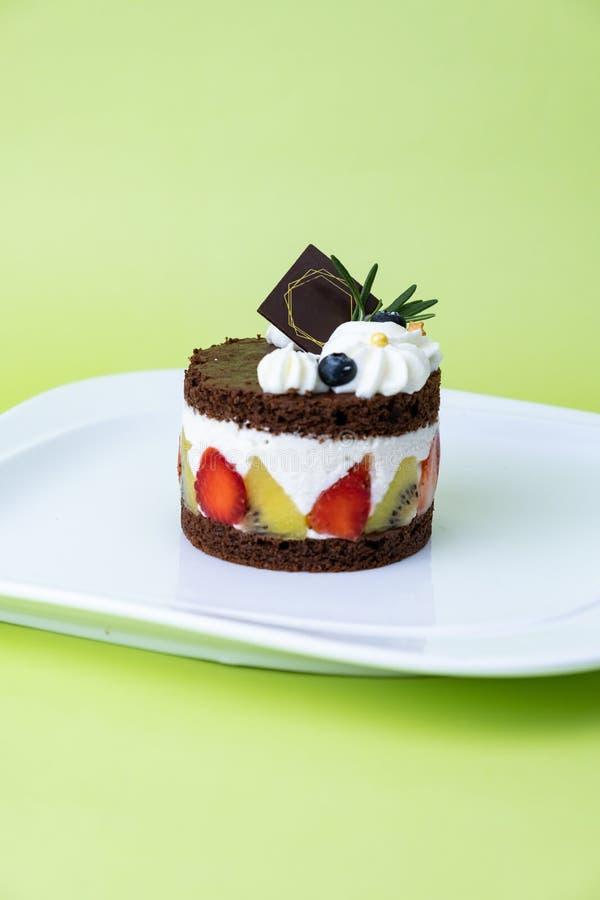 Torta de chocolate con crema y fruta del azote Fije en fondo verde fotografía de archivo