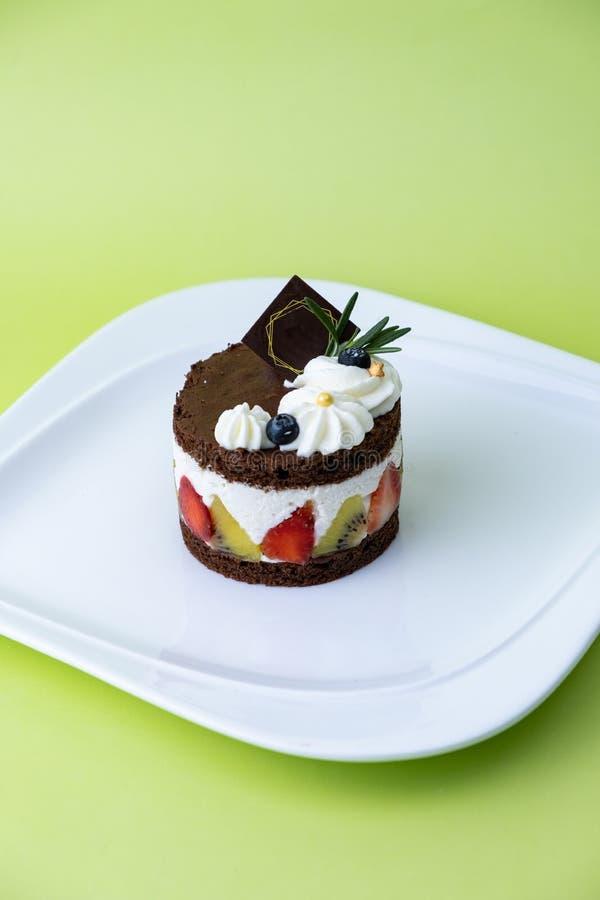 Torta de chocolate con crema y fruta del azote Fije en fondo verde foto de archivo