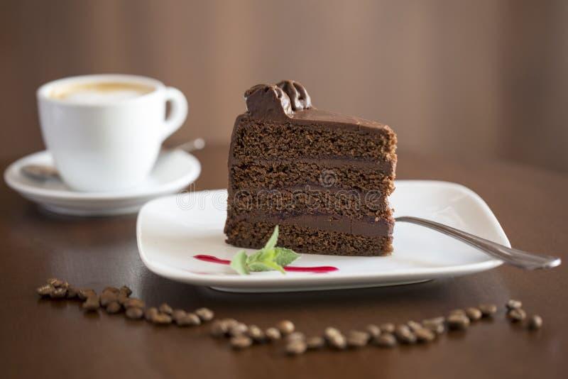 Torta de chocolate con la taza de café en el fondo - rebanada fotos de archivo libres de regalías
