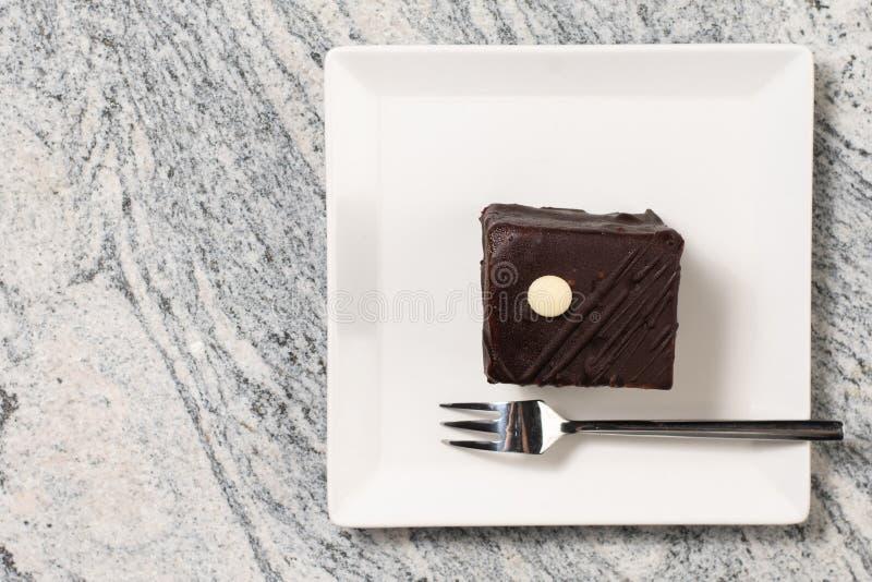Torta de chocolate con las cerezas servidas en la placa blanca cuadrada fotos de archivo libres de regalías