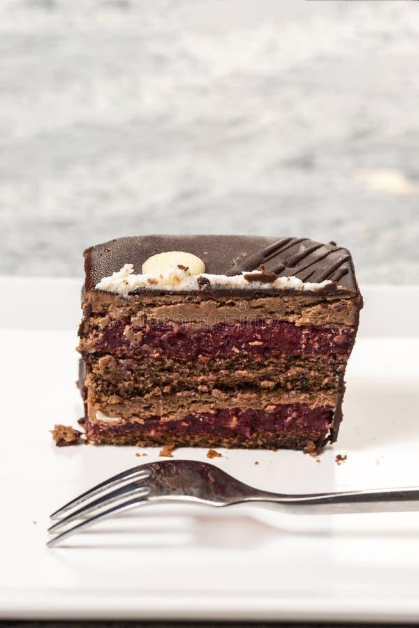 Torta de chocolate con las cerezas servidas en la placa blanca cuadrada imágenes de archivo libres de regalías