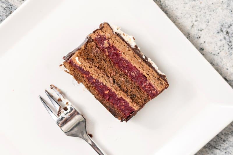 Torta de chocolate con las cerezas servidas en la placa blanca cuadrada fotografía de archivo libre de regalías