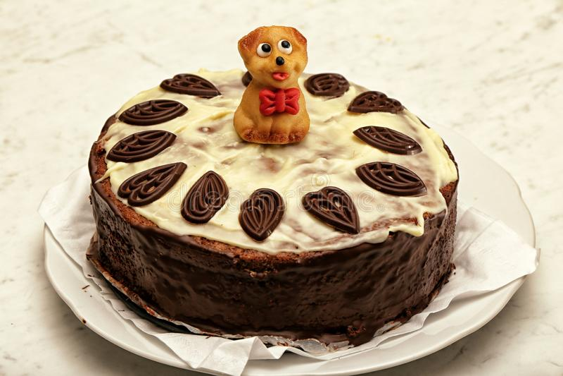 Torta de chocolate con los ornamentos y la pequeña figura del mazapán del perrito foto de archivo libre de regalías