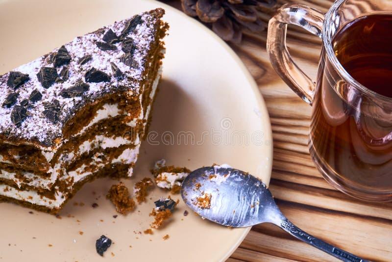 Torta de chocolate con un pedazo cortado en una placa, taza de té negro caliente fotos de archivo