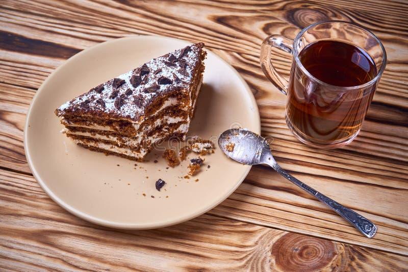 Torta de chocolate con un pedazo cortado en una placa, taza de té negro caliente foto de archivo