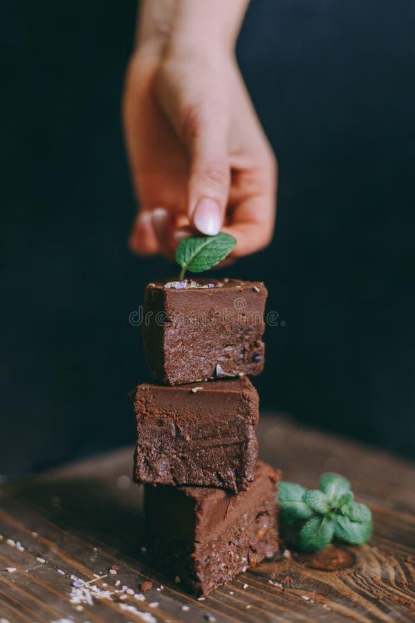 Torta de chocolate cortada con los cuadrados en un fondo negro con la mano imagenes de archivo