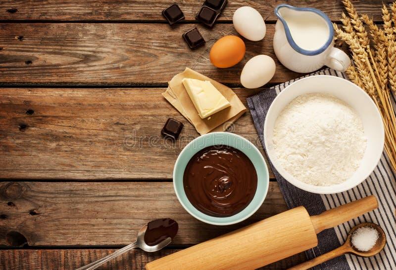Torta de chocolate de hornada - ingredientes de la receta en la madera del vintage foto de archivo