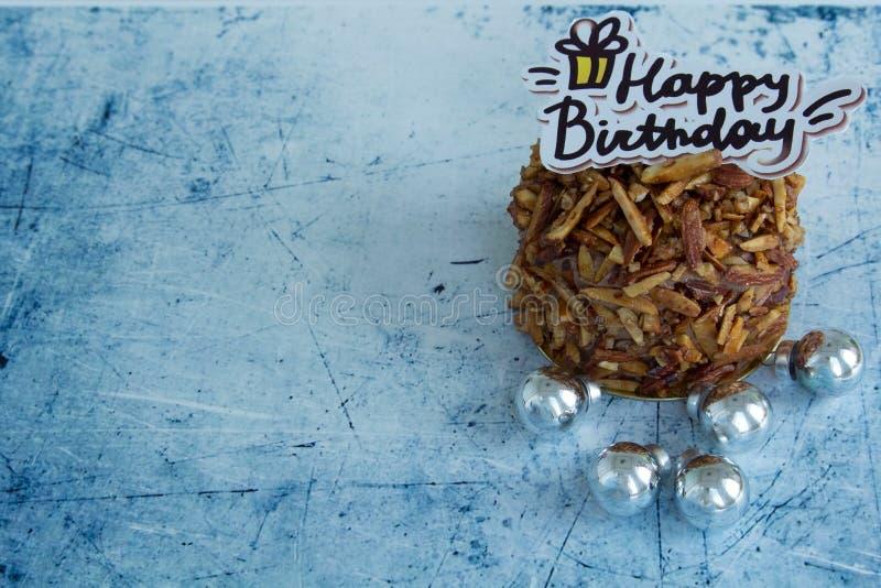Torta de chocolate de las almendras del feliz cumpleaños en fondo en colores pastel azul fotografía de archivo
