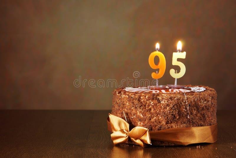 Torta de chocolate del cumpleaños con las velas ardientes como número noventa y cinco imagenes de archivo