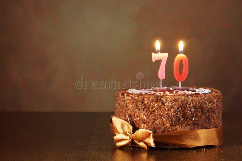 Torta de chocolate del cumpleaños con las velas ardientes como número setenta imágenes de archivo libres de regalías