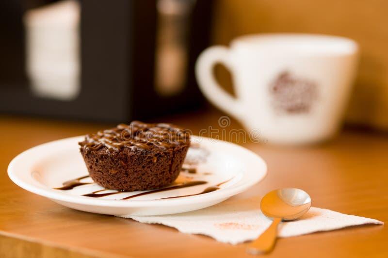 Torta de chocolate deliciosa en placa en la tabla de madera rústica con una cuchara sobre una servilleta imagen de archivo