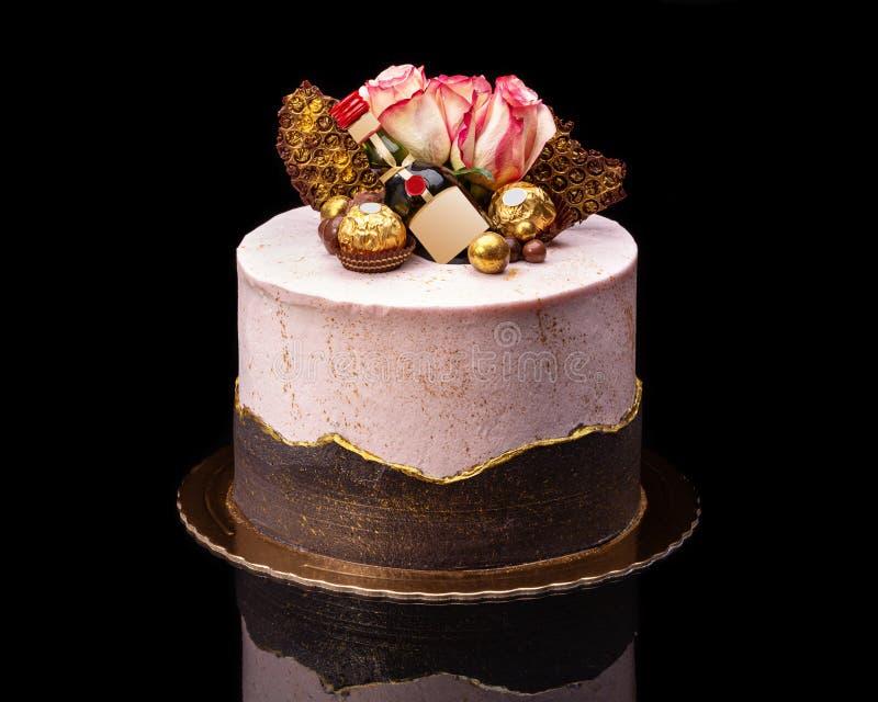 Torta de chocolate deliciosa para el día de fiesta con una botella y los chocolates imagen de archivo